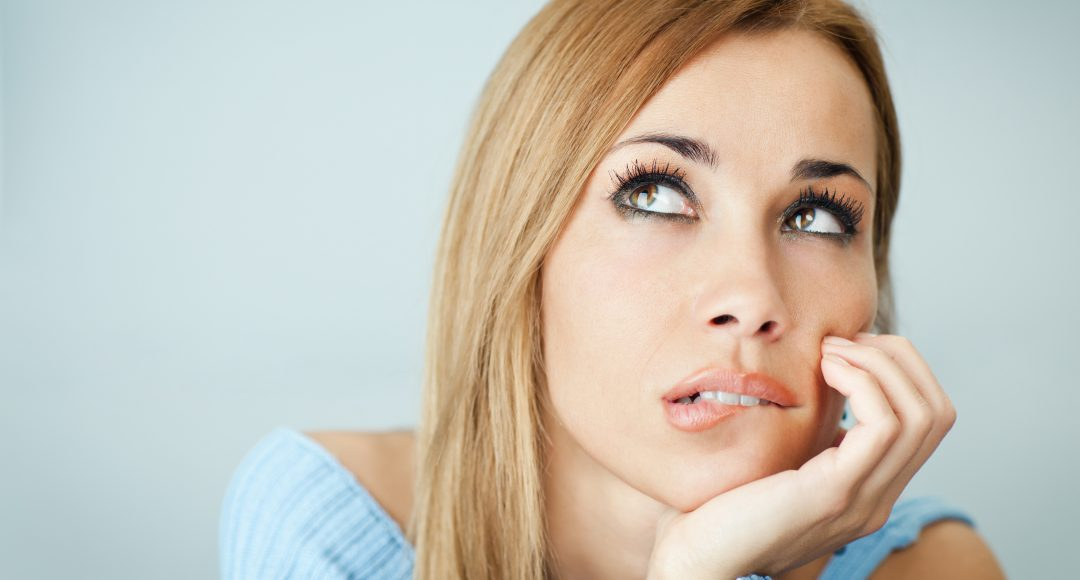 portrait of woman thinking and biting her lips, looking up with hand on cheek. Horizontal shape, Copy space